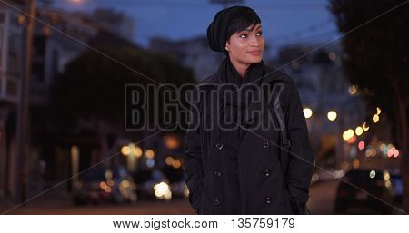 Fashionable Woman In Black Overcoat On Urban City Street At Night Smiling And Standing With Hands In