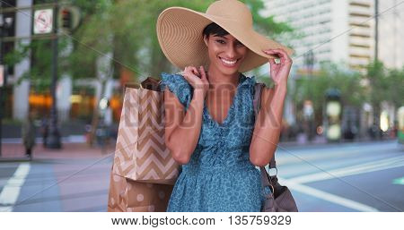 Smiling Woman With Shopping Bags Over Her Shoulder Wearing Blue Sundress And Sunhat In San Francisco