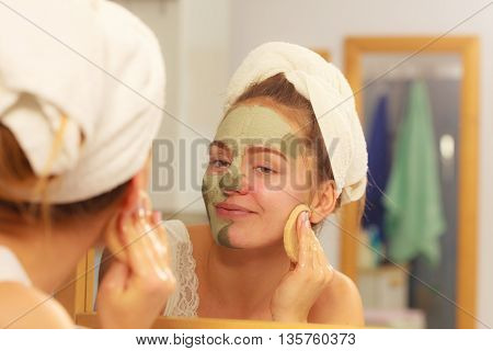 Woman Removing Facial Clay Mud Mask In Bathroom