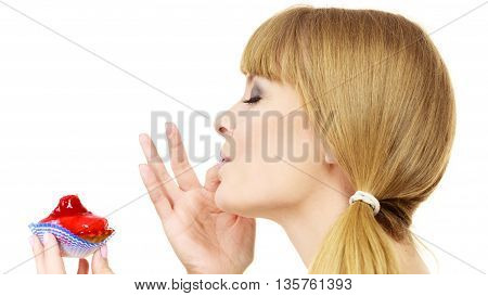 Woman holds cake cupcake in hand unhealthy food snack. Bakery sweet eating happiness and people concept. Side view