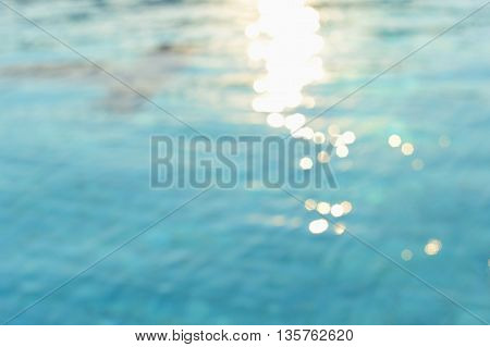 blur water in swimming pool with sunlight background