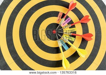 Alphabet letters hand writing words smart goals specific measurable achievable realistic timely with five dart target arrow in bullseye on dartboard, Business success concept, Abstract background