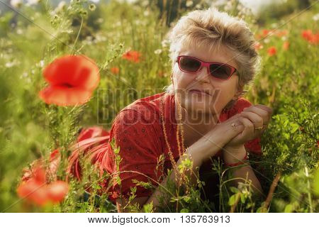 Portrait of an elderly woman in a meadow with poppies.Glamour efect.