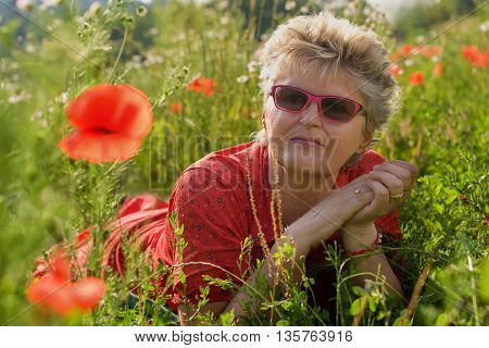 Portrait of an elderly woman in a meadow with poppies.