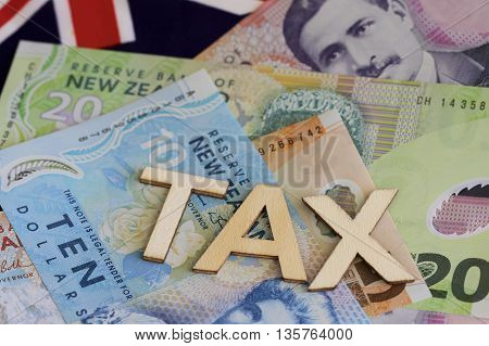 Tax sign with a background of New Zealand dollars and flag