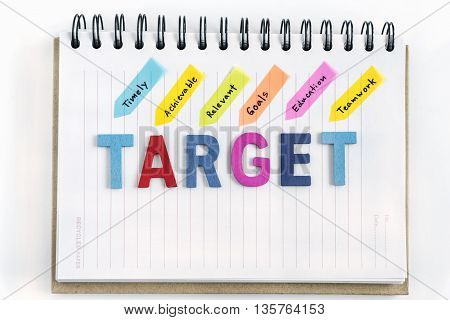 Alphabets wood letters acronyms of target word on the notebook with hand writing timely achievable relevant goals education teamwork over white background, Business success concept, Top view