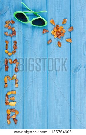 Inscription summer and shape of sun made of amber stones sunglasses on blue boards vacation time copy space for text