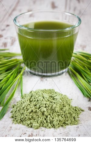 Heap Of Young Powder Barley, Barley Grass And Beverage On Old Wooden Background