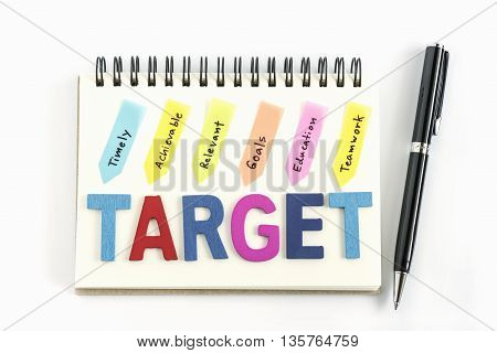 Alphabet letters words target on the notebook with handwriting timely achievable relevant goals education teamwork and pen over white background, Target customers concept
