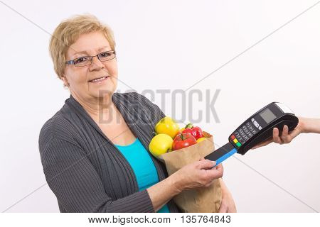 Senior Woman Holding Shopping Bag And Using Payment Terminal With Credit Card, Cashless Paying For S