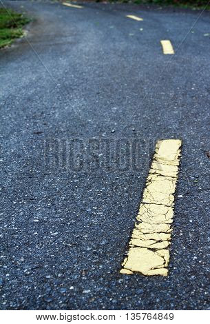 Yellow line on the road shows way not straight