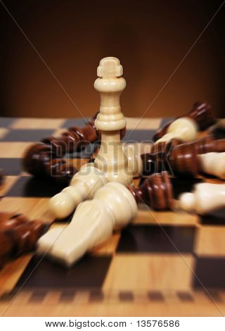 A photo of a chessboard with pieces surrounding the king