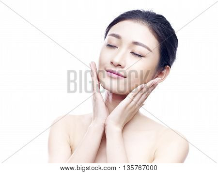 studio portrait of a young asian woman eyes closed hands on chins isolated on white.