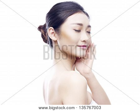 studio portrait of a young asian woman hand on chin eyes closed side view isolated on white.