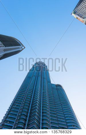 KUALA LUMPUR MALAYSIA - FEBRUARY 29: Bottom view of one of Petronas Twin Towers on February 29 2016 in Kuala Lumpur Malaysia. The modern skyscraper in business district with blue sky.