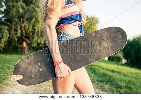 Close up skateboard. Young skateboarder girl holding skateboard.