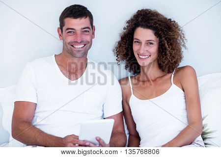 Portrait of happy couple using digital tablet on bed in bedroom