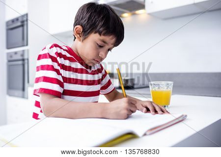 Portrait of boy doing homework in kitchen at home