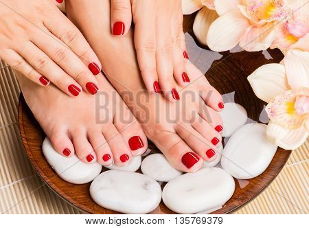 Closeup photo of a beautiful female feet at spa salon on pedicure procedure. Female legs in stone decoration the flowers.