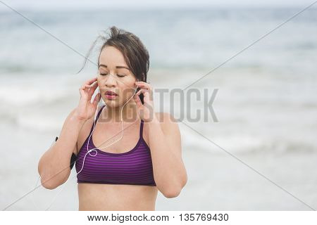 Female runner preparing for outdoor workout on the beach setting on earphones. Beautiful fit mixed race fitness model outdoors