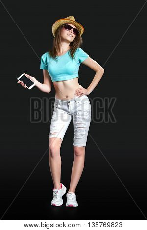 a pretty girl in a hat and sun-glasses is holding a smartphone in her hand in the black background for advertising