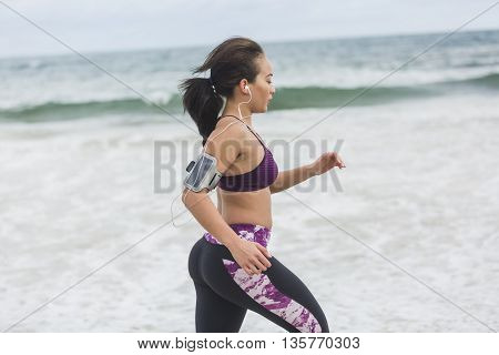 Healthy woman running on the beach, girl doing sport outdoor, happy female exercising, freedom, vacation, fitness and heath care concept with copy space over natural background
