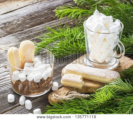 Winter breakfast ingredients. Chocolate oat cereal with marshmallows in portioned glass mugs for a cozy winter holiday nice breakfast on a background fir branches on wooden background.