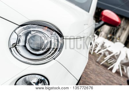 Close up of headlights of a white city car
