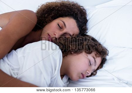 Close-up of mother and son sleeping together on bed