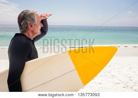 Senior man with surfboard shielding eyes at beach on a sunny day