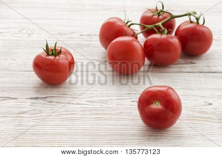 Red tomatoes. Branch of tomatoes on white wooden background. Copy space composition. Close up perspectives