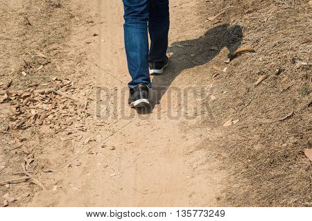 Men wear jeans and wear walking shoes on the ground.