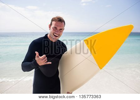 Portrait of surfer with surfboard gesturing hand sign on beach on a sunny day
