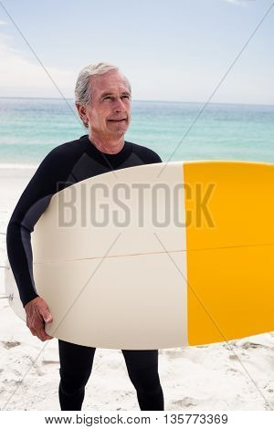 Happy senior man in wetsuit holding a surfboard on the beach