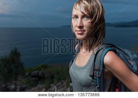 Portrait of the lady with backpack and wet clothes and hair