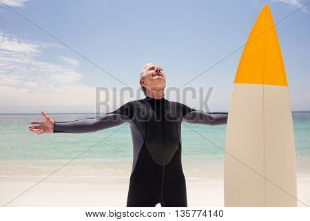 Happy senior man with surfboard standing on beach with arms outstretched