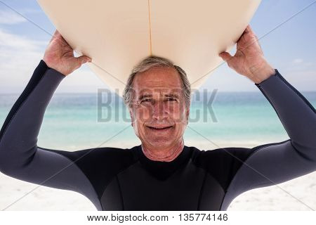 Portrait of senior man holding a surfboard over his head on the beach
