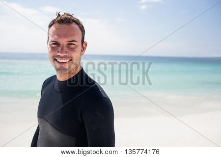 Portrait of happy surfer standing on beach on a sunny day