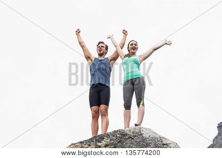 Low angle view of young couple with arms raised on rock against sky