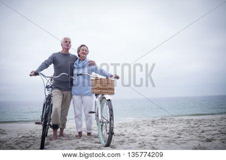 Happy senior couple with their bike on the beach