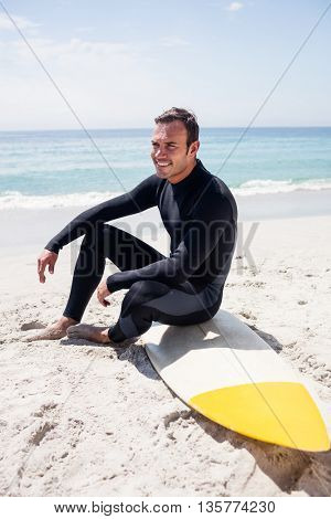 Happy surfer in wetsuit sitting with surfboard on the beach on a sunny day