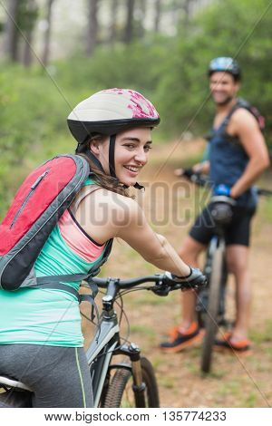 Portrait of happy female biker with man on dirt road in forest