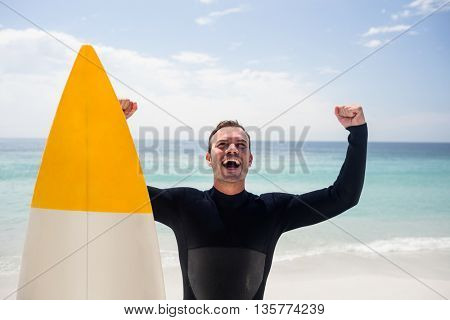 Happy man with surfboard standing on the beach with arms outstretched