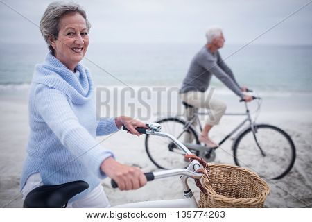 Senior couple having ride with their bike on the beach