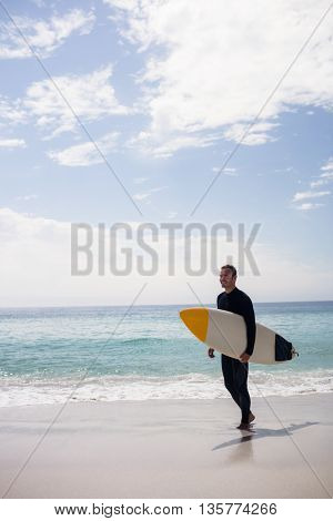 Happy surfer holding a surfboard on the beach on a sunny day