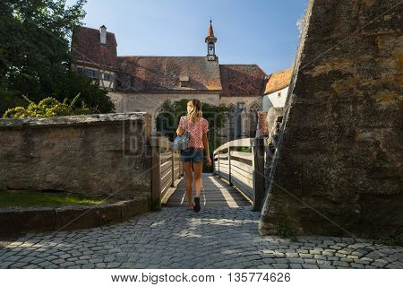 Young woman tourist walking in an old town of Rothenburg. Germany