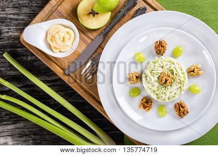 delicious a la carte salad with apples celery and nuts decorated with grapes on two white plates top view studio lighting
