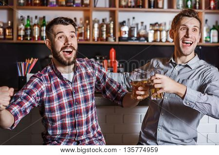 Young fun people with beer watching football in a bar