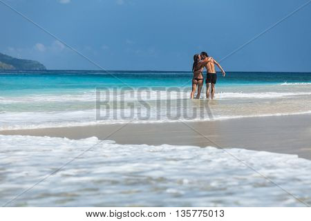 Young couple hugging and kissing on a perfect tropical sandy beach