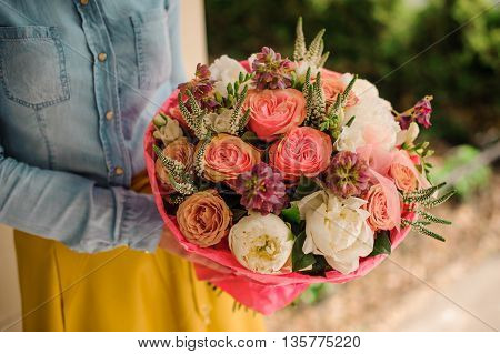 girl holding Bouquet of the different mixed orange and white flowers no face